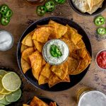 Overhead view of air fryer tortilla chips arranged in bowls with dips, beer and jalapenos surrounding it.